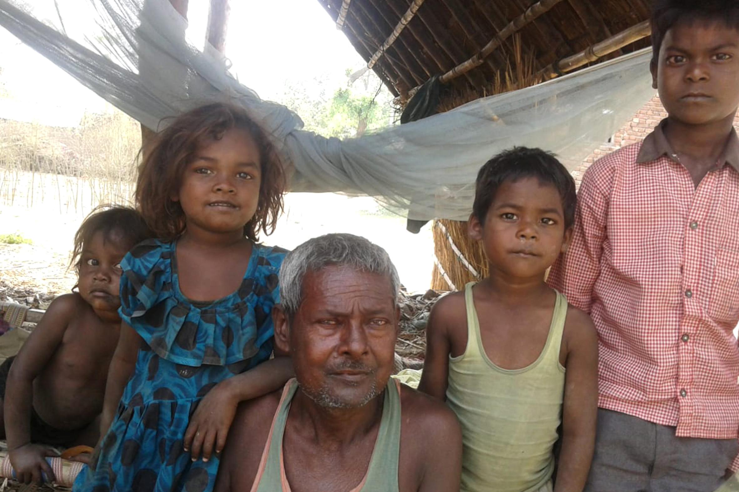 A treated kala-azar man, posing with grandchildren.