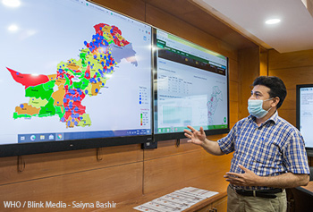 Technical officer for information management shows data on Pakistan's COVID-19 response in an operations room.
