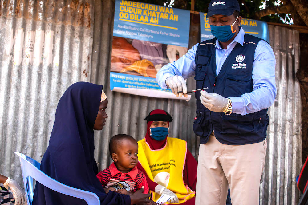 A polio zonal officer is preparing vitamin A supplement for a child during a recent integrated campaign.