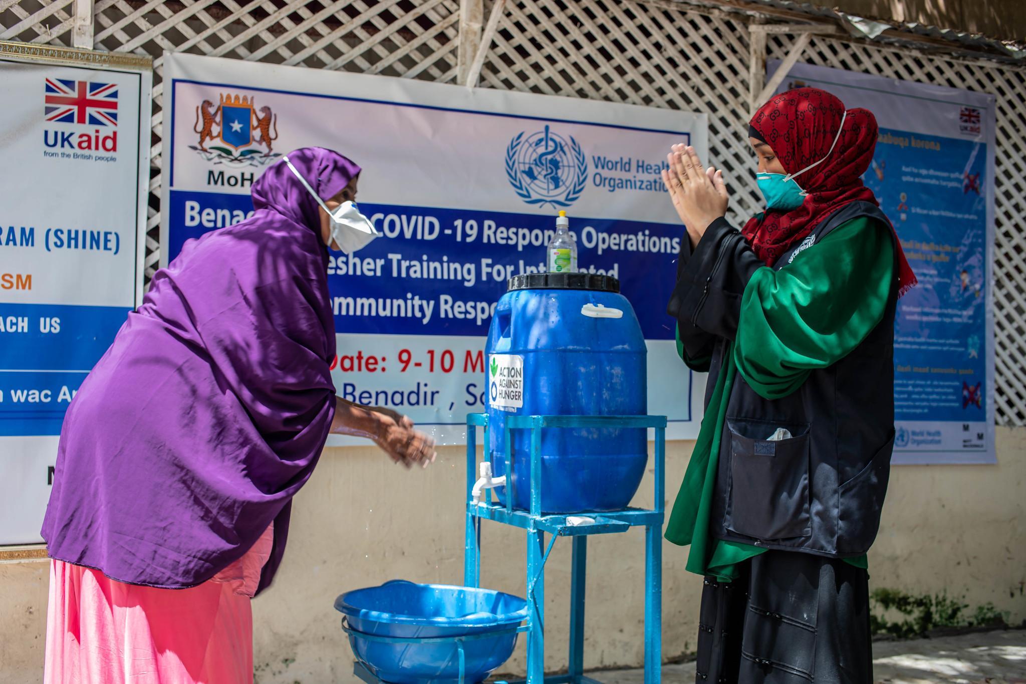 Two women washing their hands at Webari Health Facility in Benaadir Region, Somalia.