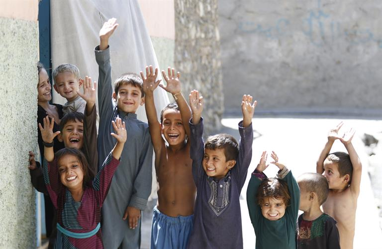 Young boys and girls raise their hands to show marks of vaccination against polio, in Afghanistan