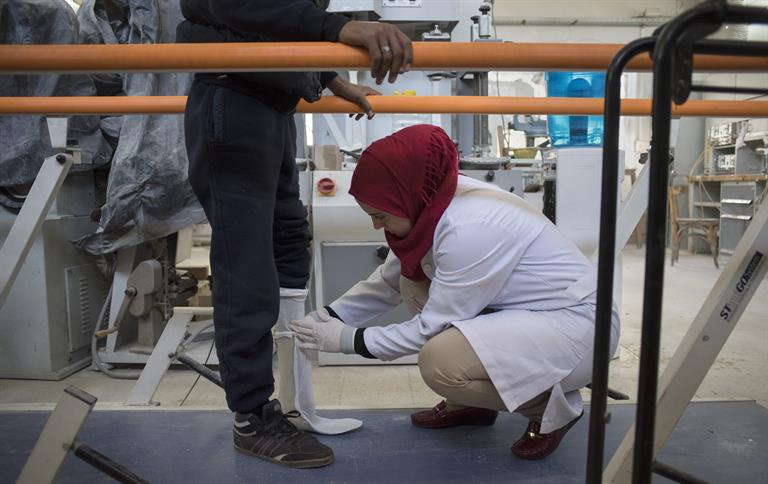 A technician fits Ismail, 17, from Qamishli, for a prosthetic foot