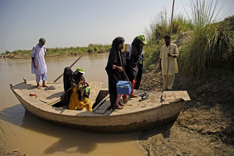A group of female vaccination volunteers get off a boat on the Indus River in Pakistan